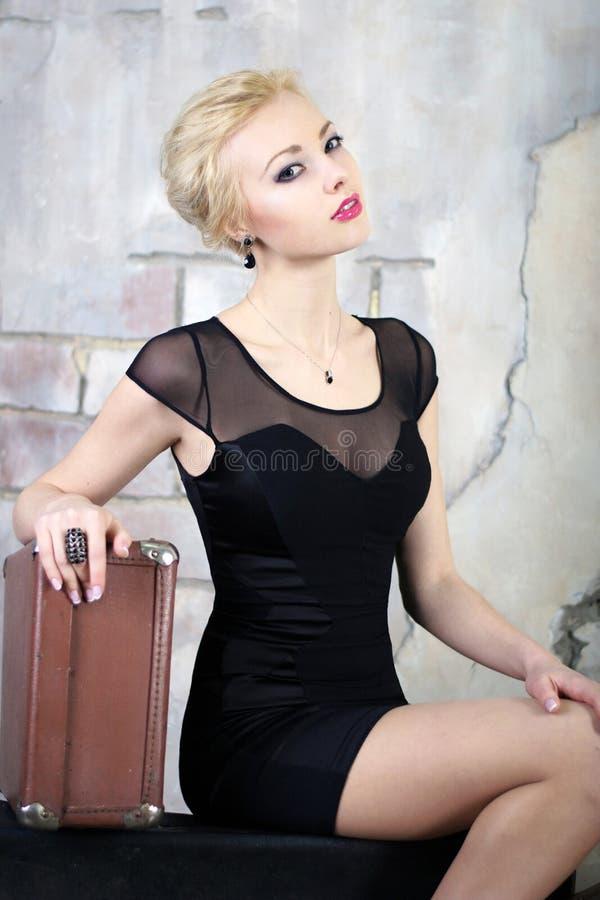 Mulher loura em um vestido preto que sorri e que guarda sua mão em um valise imagens de stock