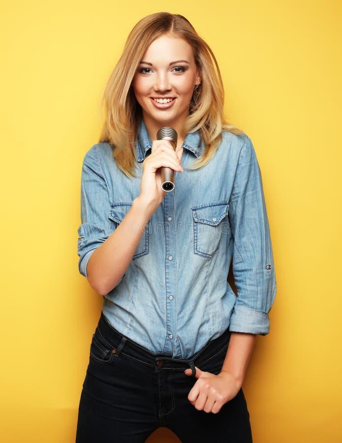 Mulher loura encantador que canta com o microfone no estúdio sobre o fundo amarelo imagens de stock