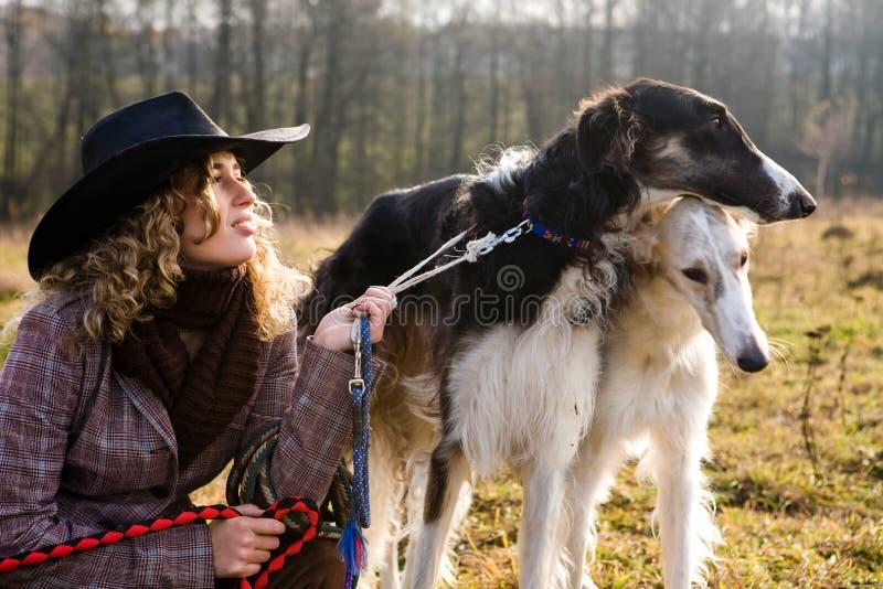 Mulher loura encantadora com dois cães em um campo fotos de stock royalty free