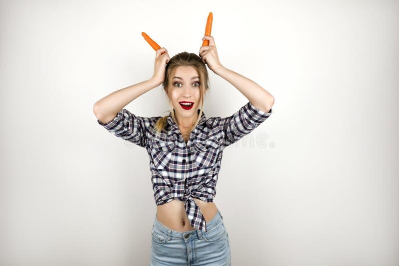 Mulher loura engraçada bonita nova que veste o short quadriculado na moda da camisa e da sarja de Nimes que põe cenouras como chi imagens de stock royalty free