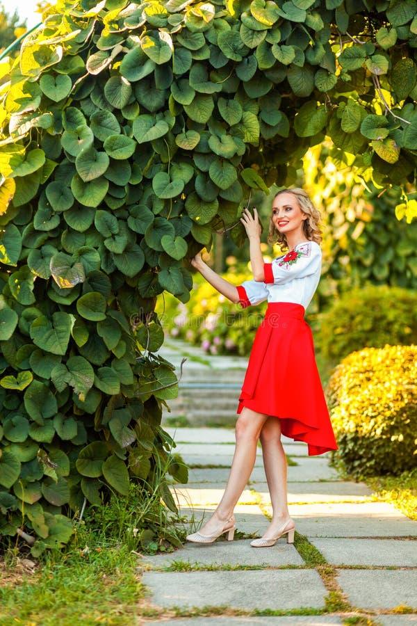Mulher loura feliz atrativa do retrato completo do comprimento no vestido branco vermelho à moda que levanta perto do arco floral imagens de stock royalty free