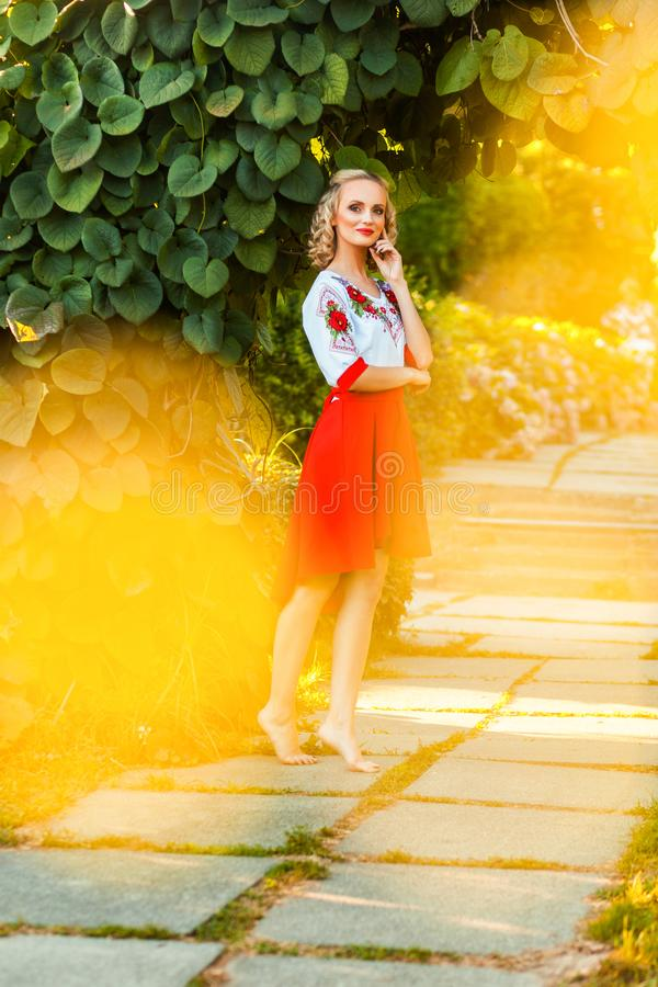 Mulher loura feliz bonito do retrato completo do comprimento no vestido branco vermelho à moda que levanta perto do arco floral n fotografia de stock royalty free