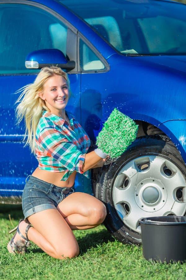 A mulher loura feliz lava o carro imagem de stock