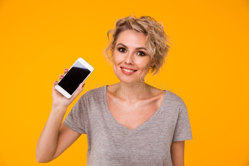 Mulher loura feliz na camiseta que mostra a tela vazia do smartphone e que aponta nela ao olhar a câmera com aberto foto de stock royalty free