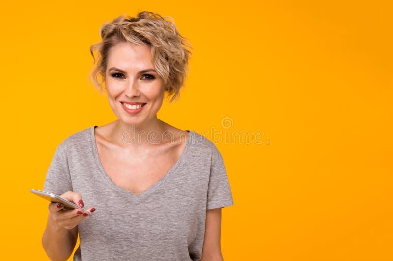 Mulher loura feliz na camiseta que mostra a tela vazia do smartphone e que aponta nela ao olhar a câmera com aberto fotografia de stock royalty free