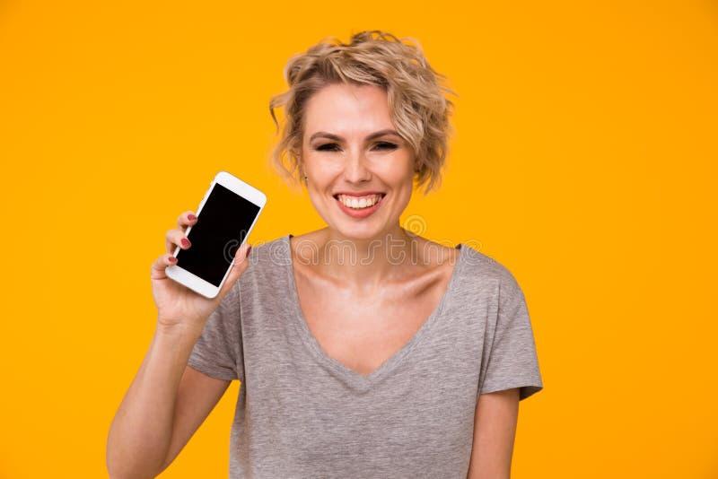 Mulher loura feliz na camiseta que mostra a tela vazia do smartphone e que aponta nela ao olhar a câmera com aberto imagem de stock