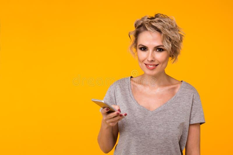 Mulher loura feliz na camiseta que mostra a tela vazia do smartphone e que aponta nela ao olhar a câmera com aberto fotos de stock
