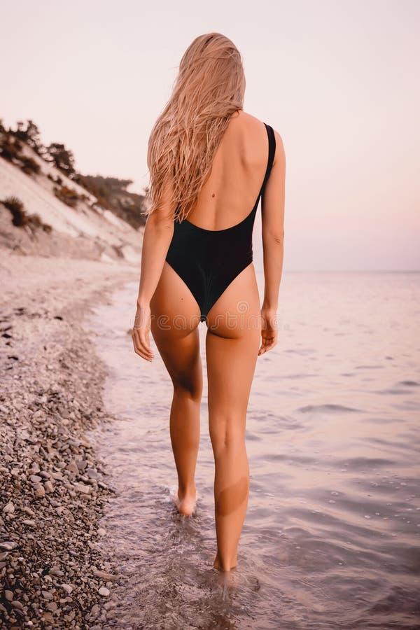 Mulher loura feliz na corrida preta do roupa de banho e jogo na praia do mar com cores mornas do por do sol foto de stock royalty free