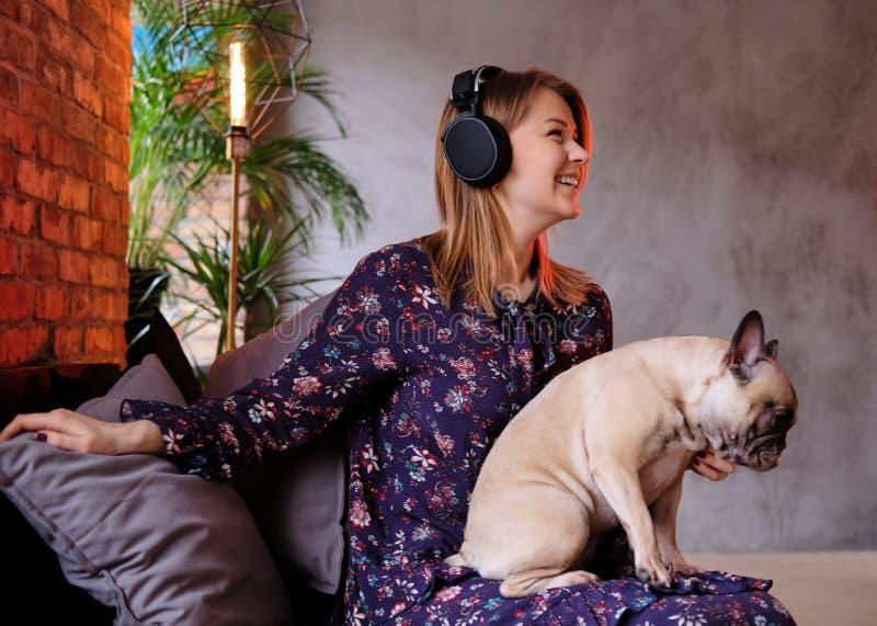 Mulher loura feliz no vestido que senta-se com seu pug bonito em um sofá feito a mão e que escuta a música em uma sala com sótão fotografia de stock