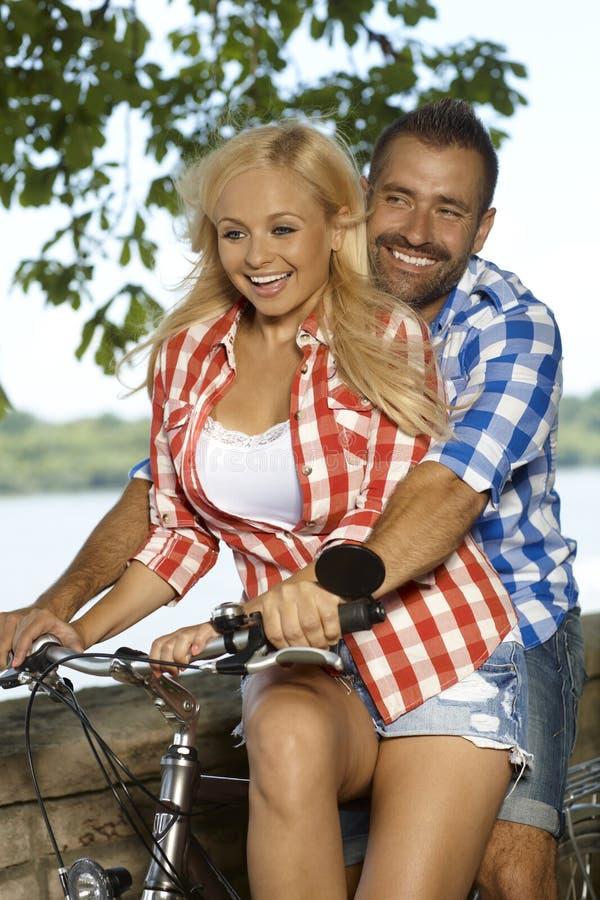 Mulher loura feliz que obtém um elevador da bicicleta exterior fotos de stock royalty free