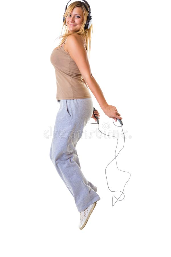 Mulher loura feliz que salta na corda de salto fotografia de stock