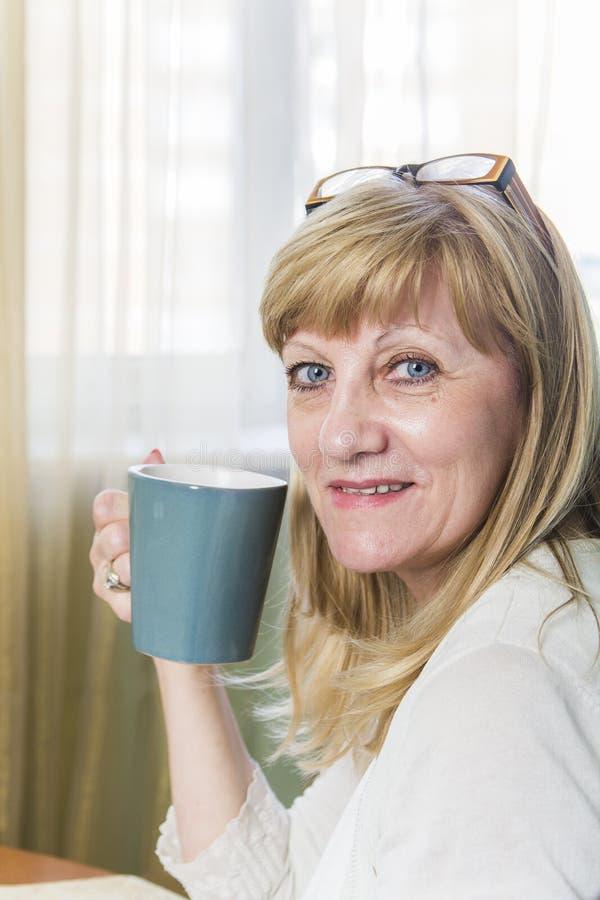 Mulher loura feliz superior que guarda a xícara de café foto de stock