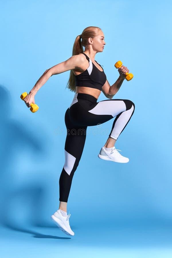 Mulher loura forte apta que faz exercícios com pesos fotos de stock