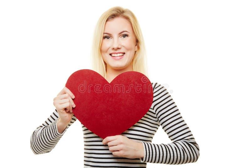A mulher loura guarda o coração para o dia do ` s da mãe imagens de stock