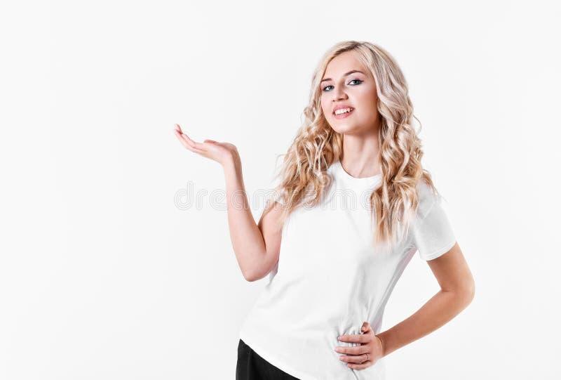 A mulher loura guardara um objeto imagin?rio em uma m?o em um fundo branco Espa?o livre para anunciar de seu produto fotografia de stock royalty free