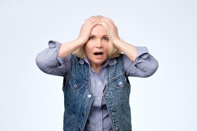 Mulher loura idosa ansiosa que frustra a expressão forçada foto de stock royalty free
