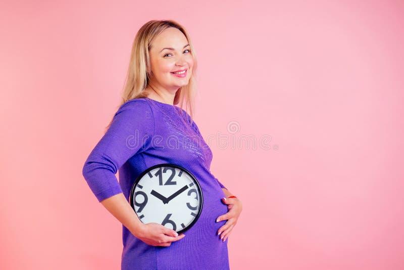 Mulher loura linda e sorridente segurando um relógio em mãos no estúdio em um fundo rosa tempo de nascimento imagens de stock royalty free