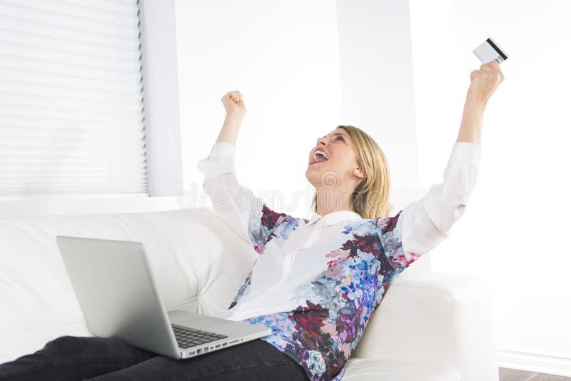 Mulher loura lindo que descansa em um sofá branco em casa e que usa um portátil fotos de stock royalty free
