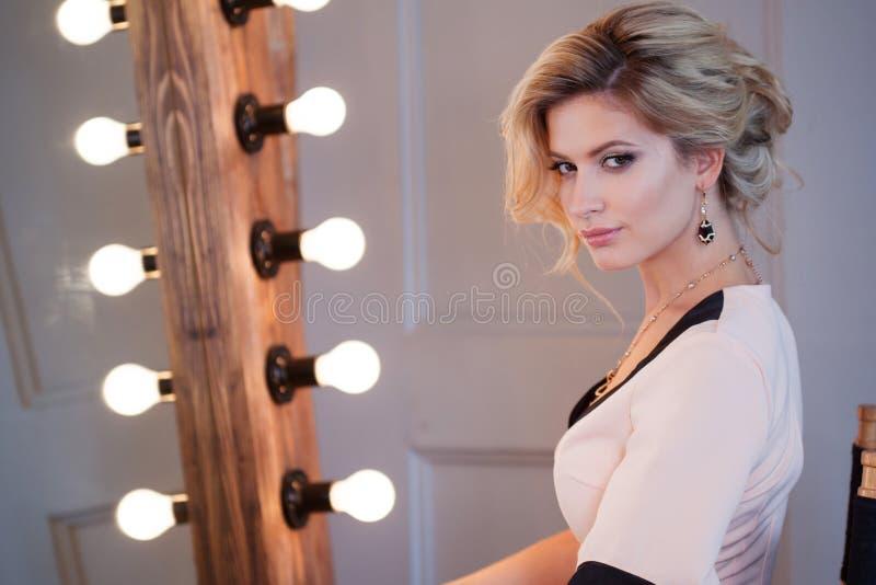 Mulher loura luxuosa da beleza Modelo novo atrativo no vestido bonito que senta-se na frente do espelho, ao primp imagens de stock royalty free
