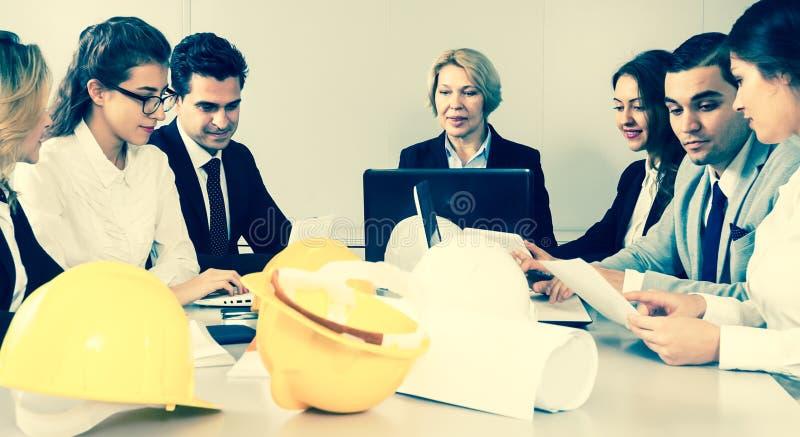 A mulher loura madura conduz a reunião dos arquitetos fotos de stock