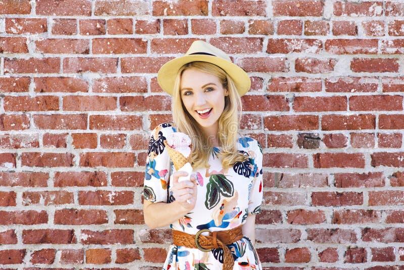 Mulher loura milenar com suportes de um cone de gelado contra uma parede de tijolo em um dia de verão foto de stock royalty free