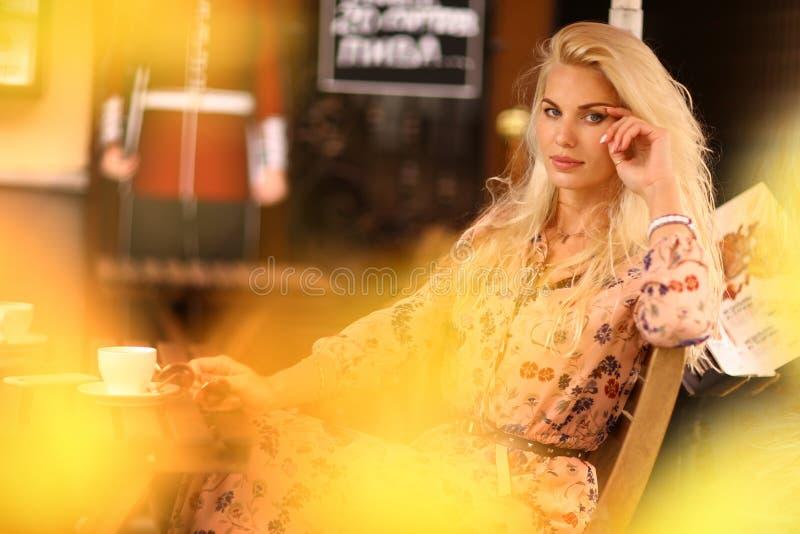 A mulher loura na pausa para o almoço senta-se no café exterior do verão com copo o imagem de stock