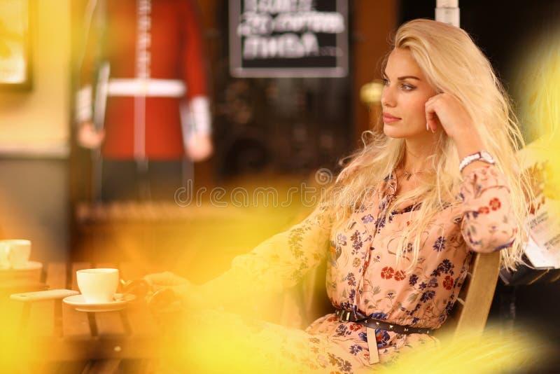 A mulher loura na pausa para o almoço senta-se no café exterior do verão com copo o fotografia de stock royalty free