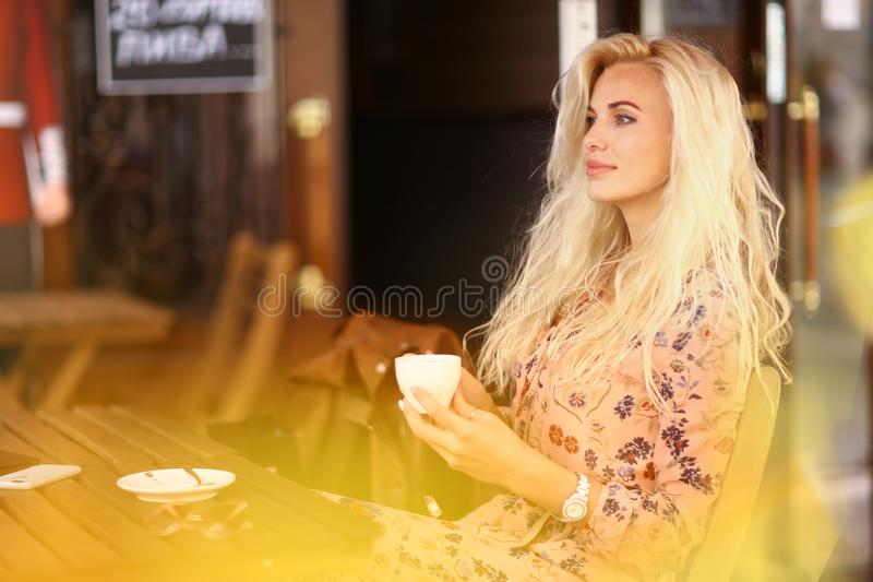 A mulher loura na pausa para o almo?o senta-se no caf? exterior do ver?o com copo o fotos de stock royalty free