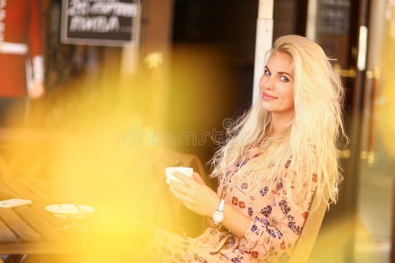 A mulher loura na pausa para o almo?o senta-se no caf? exterior do ver?o com copo o imagens de stock royalty free