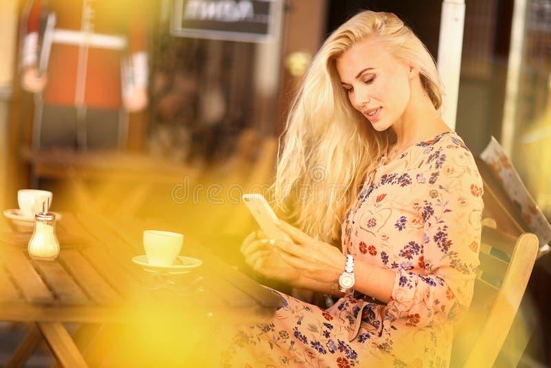 A mulher loura na pausa para o almo?o senta-se no caf? exterior do ver?o com copo o foto de stock