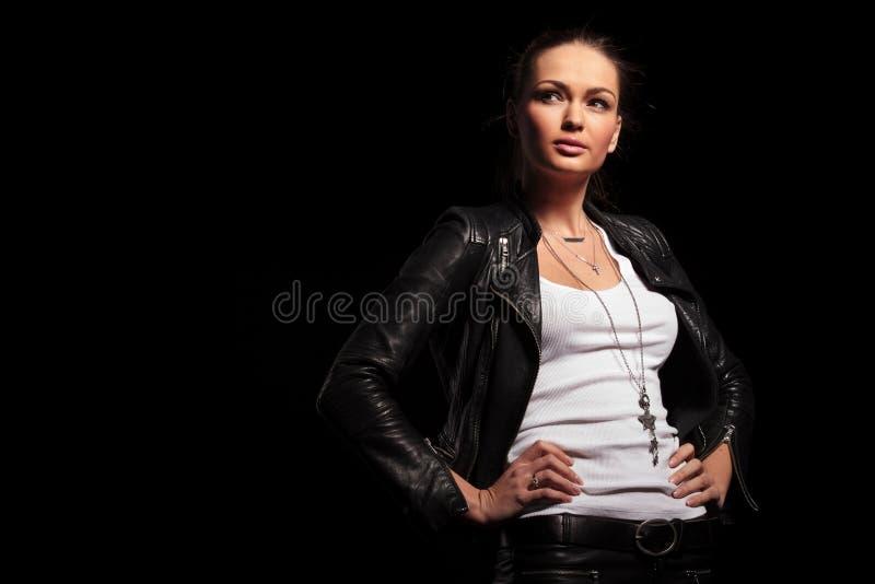 Mulher loura na roupa de couro que está com mãos no wais imagem de stock royalty free