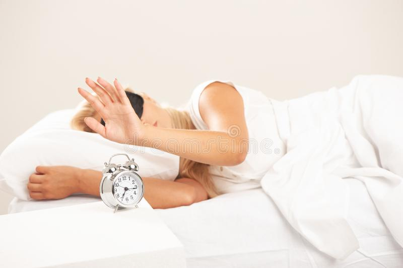 A mulher loura na vista da cama irritou em seu despertador fotografia de stock