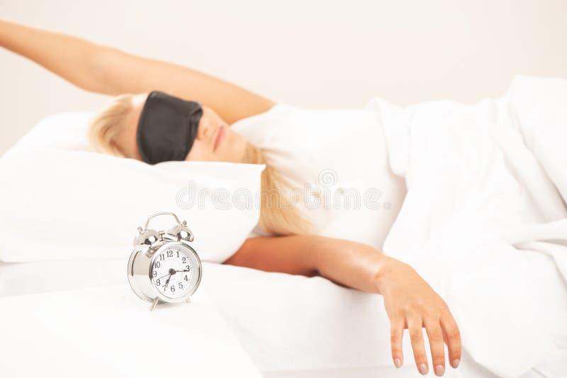A mulher loura na vista da cama irritou em seu despertador imagem de stock royalty free