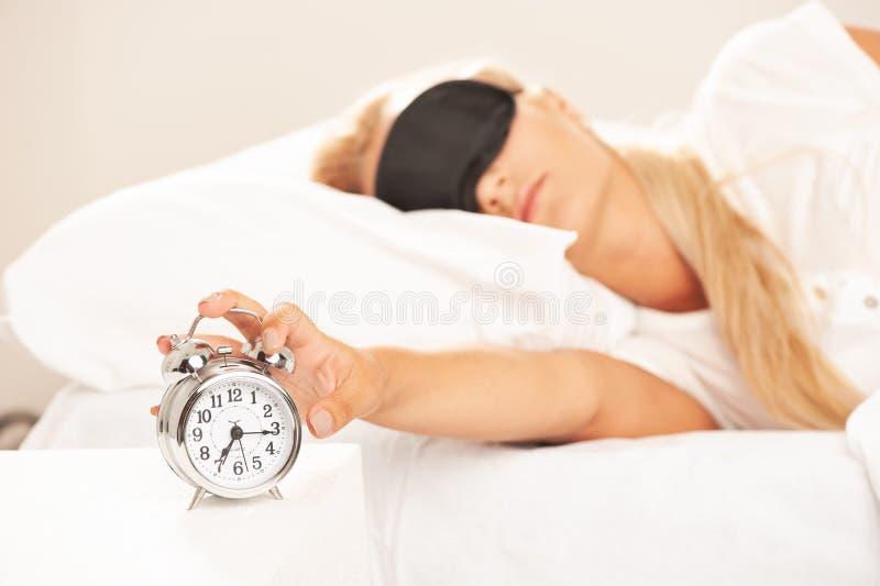 A mulher loura na vista da cama irritou em seu despertador foto de stock