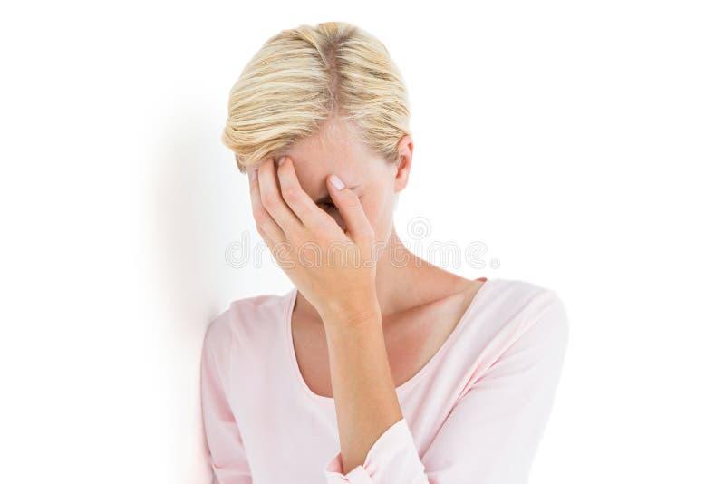 Mulher loura nervosa que cobre sua cara fotos de stock royalty free