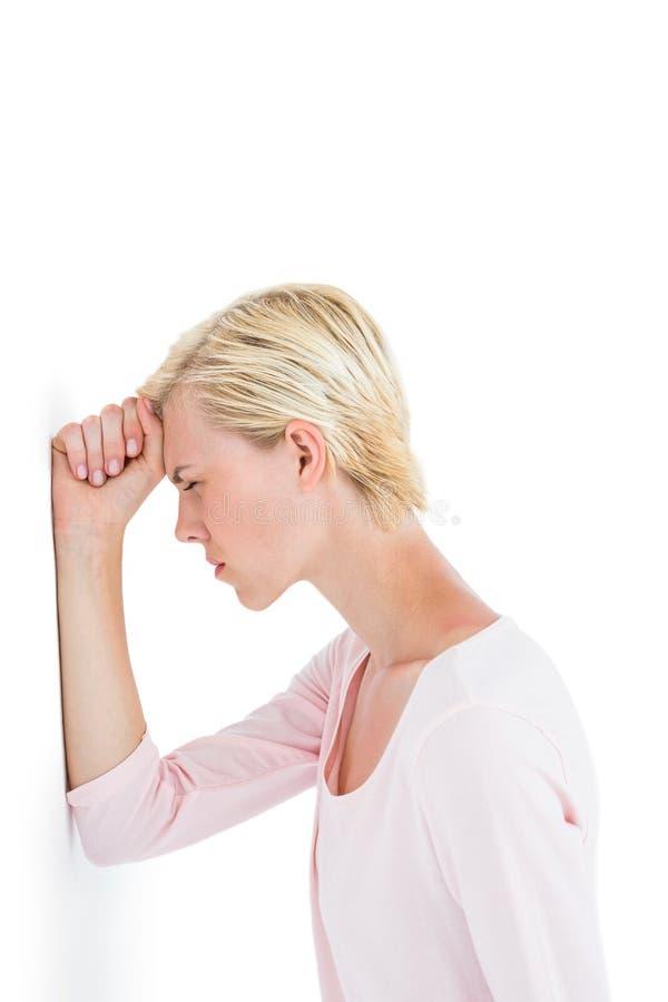 Mulher loura nervosa que inclina-se contra a parede foto de stock