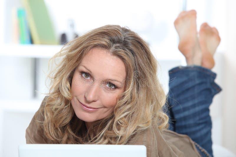 Mulher loura no portátil imagens de stock