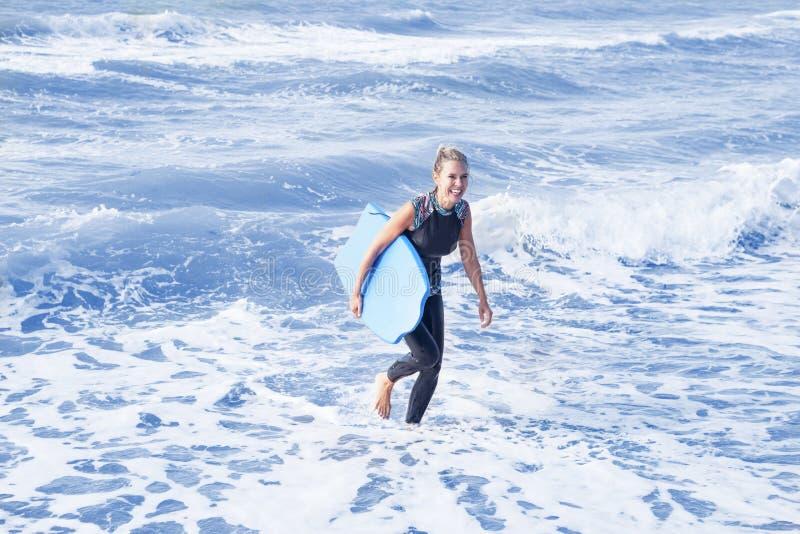 A mulher loura no roupa de mergulho e a natação embarcam na água foto de stock