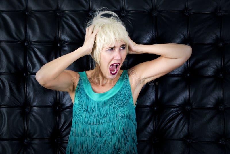 A mulher loura no vestido verde está gritando fotos de stock
