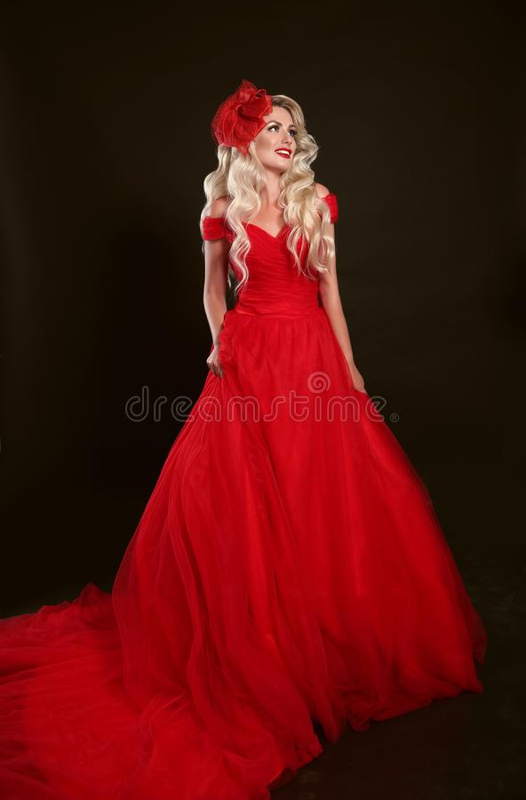 Mulher loura no vestido vermelho e no chapéu elegante isolados no bla do estúdio fotografia de stock royalty free