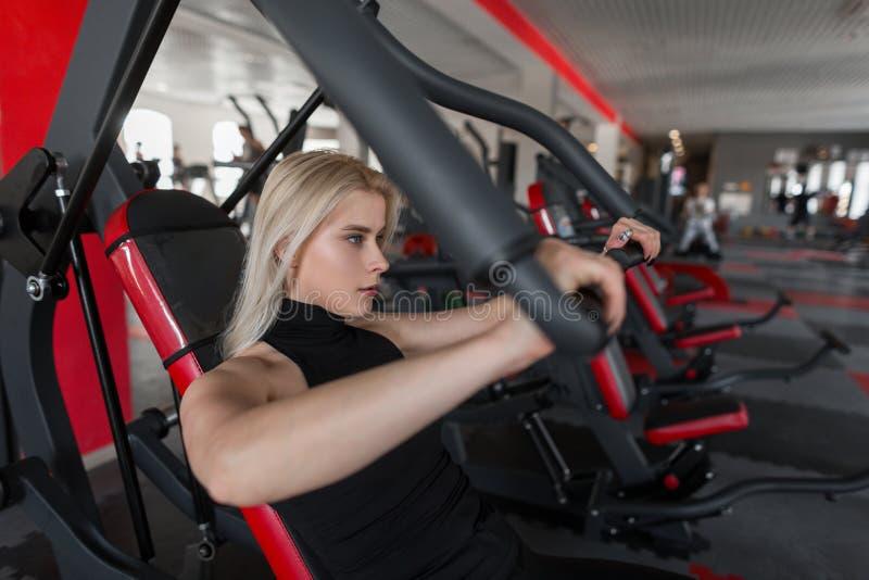 Mulher loura nova atrativa no sportswear preto no treinamento no gym A menina faz exercícios para as mãos imagens de stock