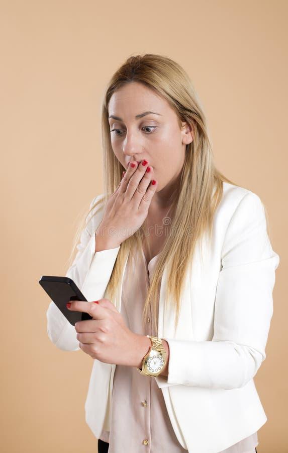 A mulher loura nova atrativa usa o smartphone e é surpreendida imagem de stock royalty free