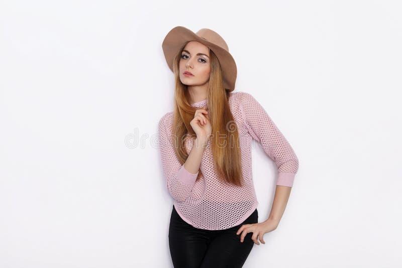 Mulher loura nova bonita bonito e à moda em poses modelo praticando da roupa na moda e vista afastado com sorriso ao estar imagens de stock