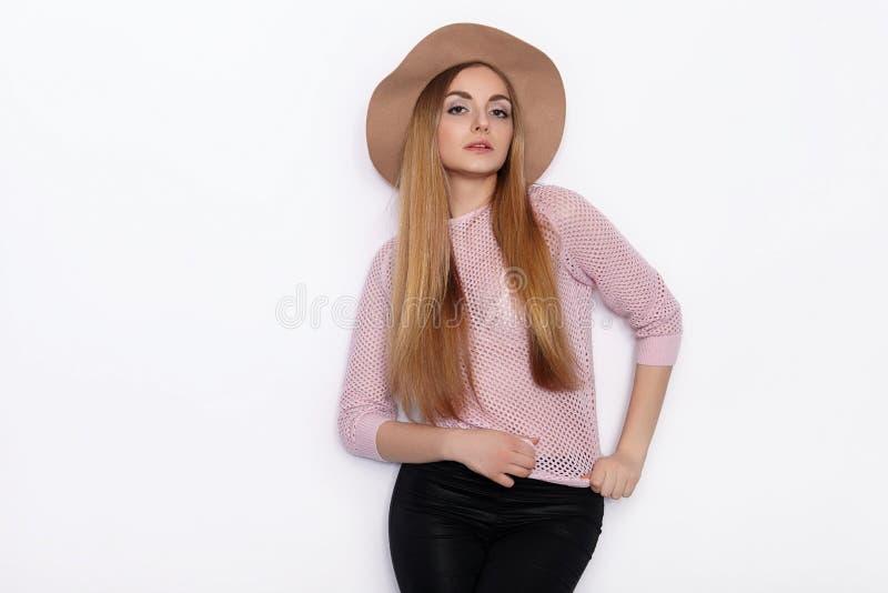 Mulher loura nova bonita bonito e à moda em poses modelo praticando da roupa na moda e vista afastado com sorriso ao estar foto de stock