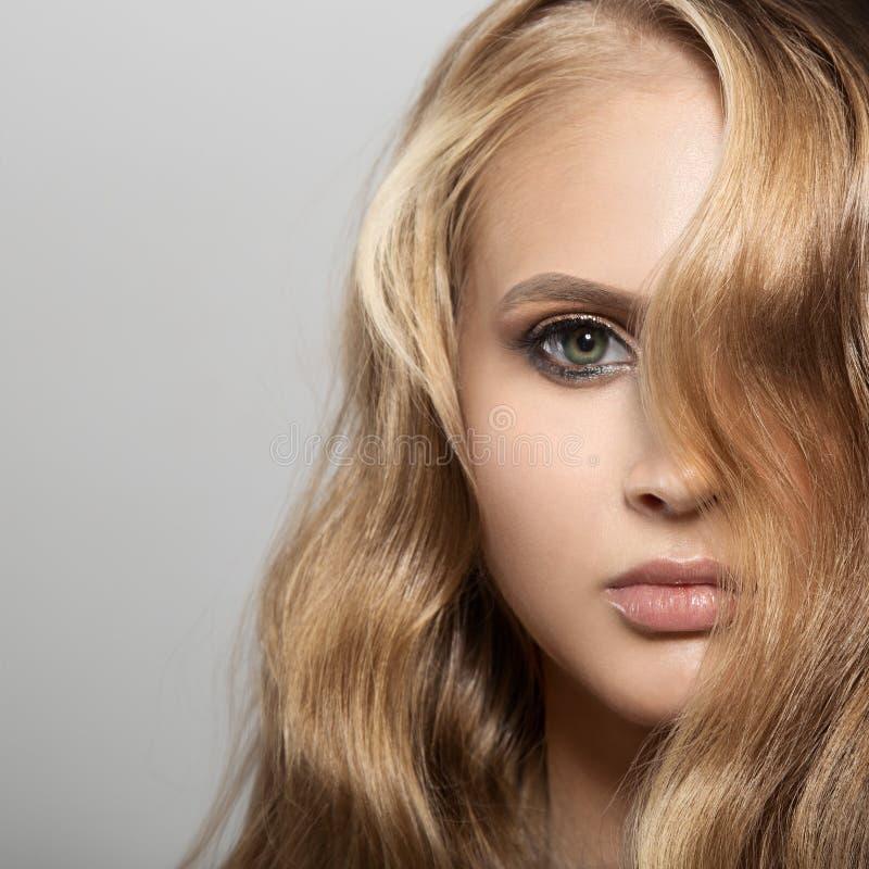 Mulher loura nova bonita com cabelo ondulado longo foto de stock