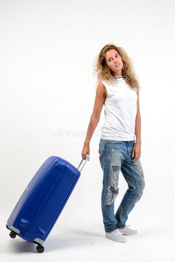 Mulher loura nova bonita com a mala de viagem plástica azul no branco fotografia de stock royalty free
