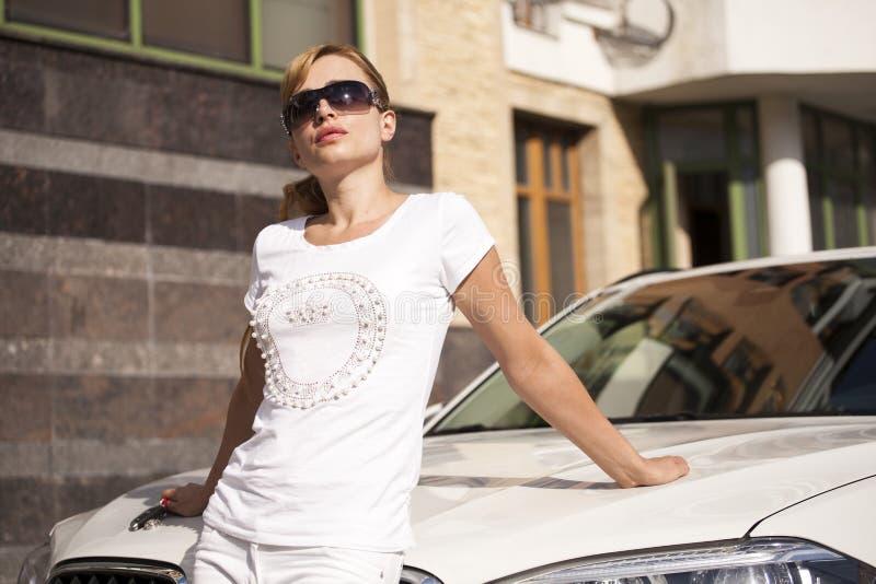 Mulher loura nova bonita com os óculos de sol sobre o carro foto de stock