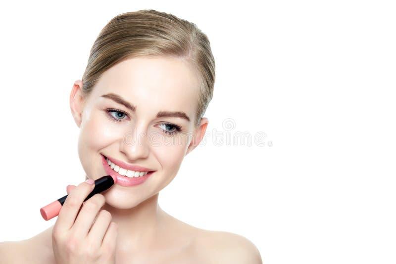 Mulher loura nova bonita com os bordos completos 'sexy' que aplicam o batom coral da cor imagens de stock
