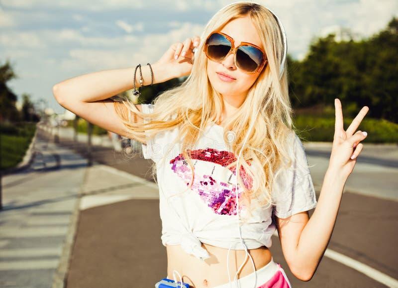 Mulher loura nova bonita do verão em óculos de sol do vintage que escuta a música com fones de ouvido, sinal da vitória da mostra fotos de stock