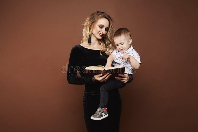 Mulher loura nova bonita e feliz no vestido preto elegante com um bebê pequeno bonito na sua leitura das mãos fotos de stock